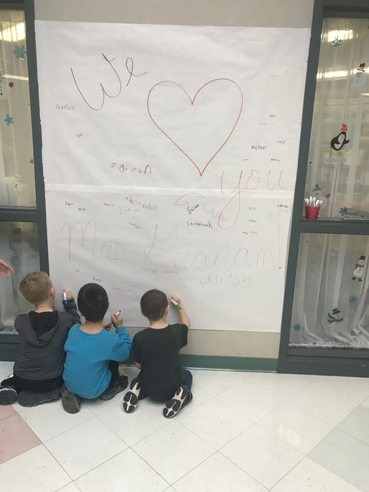 SES students signing the poster for Mrs. Graham.