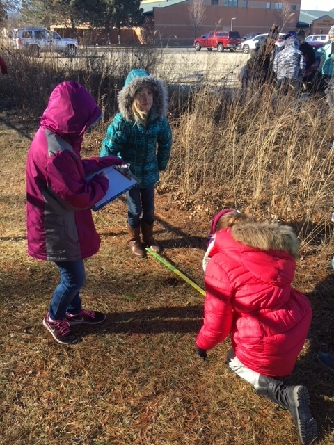 Fourth graders Anna, Lily, and Aubrey use a measuring tape to measure the perimeter of our garden.